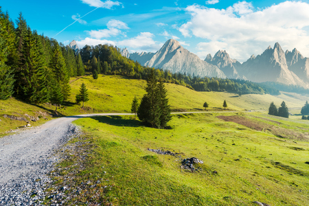 country road winds through the valley. mountains with high rocky peaks in the distance. composite image of a beautiful landscape at hazy sunrise Stock Photo