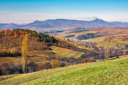 lovely countryside in autumn. village in the nearest mountain and mountain ridge with high peak in the distance. sunny weather Stock Photo