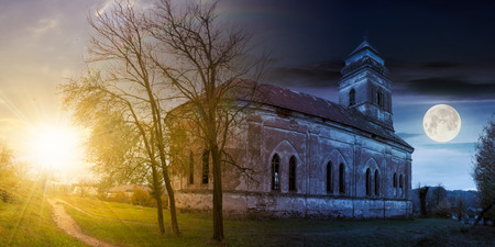 time change concept with sun and moon. panorama of abandoned catholic church on hill Stock Photo - 109273741