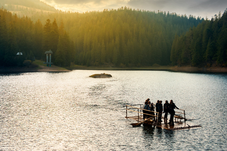 Synevir, Ukraine - OCT 20, 2008: group of young tourists on a wooden raft in the middle of a lake. gorgeous evening light above the forest on hill in the distance. wonderful atmosphere of autumn Stock Photo - 109267190