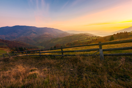 beautiful sunrise in mountains. wonderful countryside scenery in autumn. fence along the rural fields. fog in the distant valley Banco de Imagens - 109273798