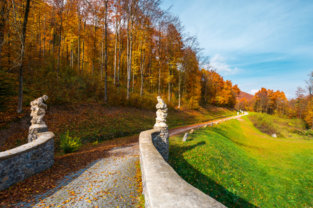 path from the stone bridge in to the forest. trees in fall colors. blue sky above the landscape Stock Photo