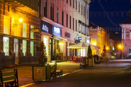Uzhgorod, Ukraine - OCT 25, 2014: Korzo street in evening. main street of the old town. popular tourist destination and meeting place for local people Editorial