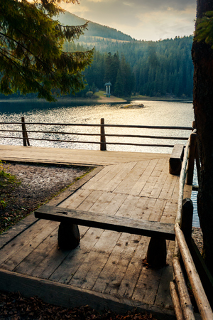 wooden bench on the pier of a Synevyr lake. beautiful autumn evening Stock Photo - 109273828