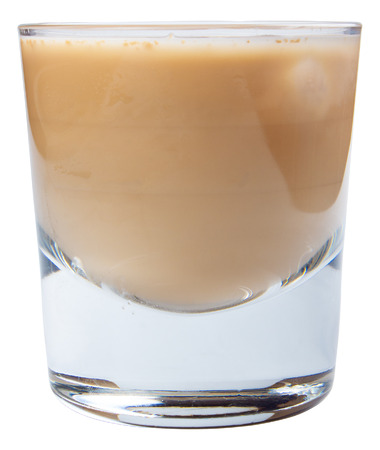 irish cream alcohol cocktail with ice in a short glass. side view isolated on a white background