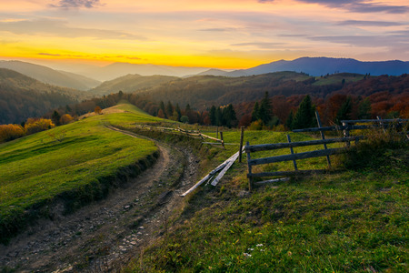 sunset in autumn mountains. winding country road through grassy rural hill. wooden fence along the path. trees in fall foliage. distant ridge in evening haze