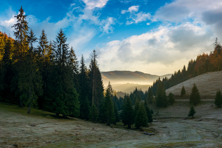 mysterious countryside in mountains. wonderful autumn weather with gorgeous sky and fog in distant valley