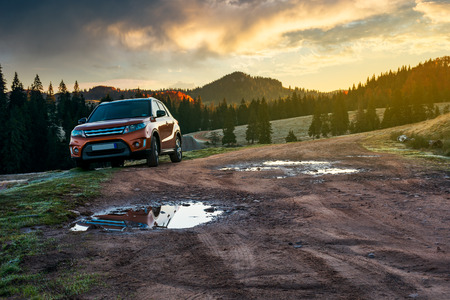 orange suv parked on the country road near forest in mountains at sunrise. beautiful autumn scenery. travel Europe by car concept Stock Photo - 109273841