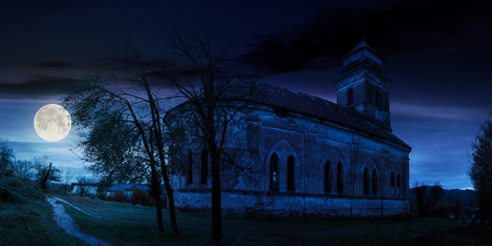 panorama of abandoned catholic church on hill at night in full moon light Stock Photo