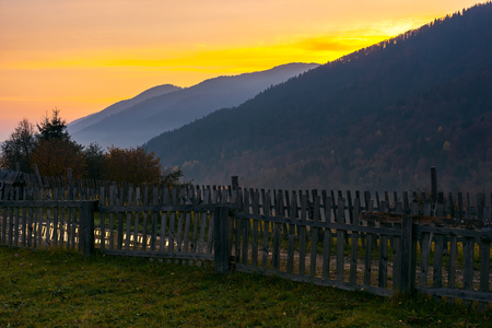 village outskirts in mountains at dawn. wooden fence along the road with puddle. deep autumn weather Stock Photo
