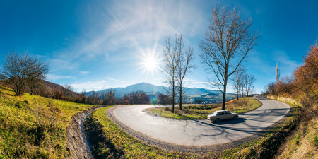 panorama of winding serpentine road. lovely autumn afternoon with bright sun on a blue sky. leafless trees by the road. village in valley and ridge in the distance. fast moving car uphill
