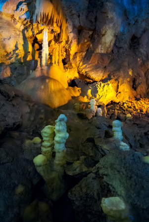 cave with colorful textured walls and stalactites and stalagmite