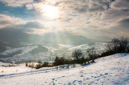magical winter countryside. sun ray through the cloudy sky. snowy hill and leafless trees. village down in the valley Stock Photo