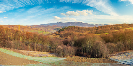 panorama of mountainous countryside in late autumn. almost leafless forest on hill. gorgeous cloudscape above the ridge with high peak in snow in the distance Stock Photo