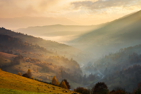 amazing glowing sunrise in mountains. countryside in fall colors. village down in the valley in haze and fog