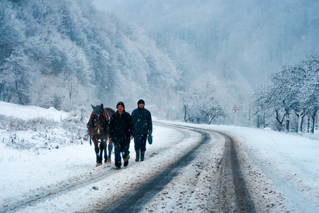 Kostryna, Ukraine - DEC 2, 2007: two men with a horse on the mountain road in winter. horrible weather. transportation problem concept