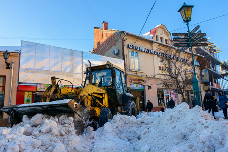Uzhgorod, Ukraine - January 19, 2017: snow removal on streets of old town. people remove snow huge amount of snow with the help of  tractor with snowplow