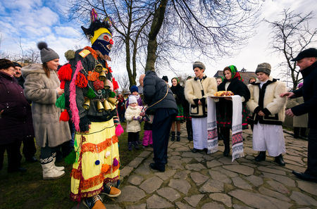 Uzhgorod, Ukraine - Jan 13, 2018: Vasylya festival celebrating in Museum of Folk Architecture and Life. local Romanians and clown meet governor with traditional bread and salt while he give sweets to kids Editorial