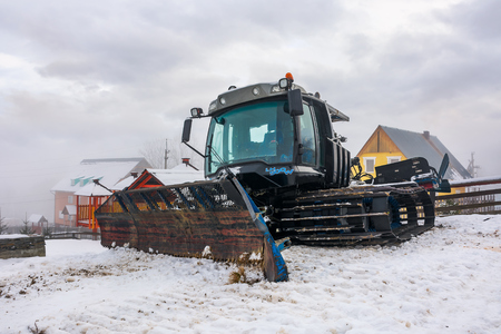 Pylypets, Ukraine - DEC 21, 2016: snow groomer parked in the resort village. huge machinery without a work on a cloudy winter day Editorial
