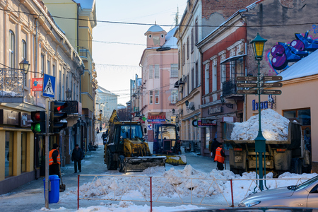 Uzhgorod, Ukraine - January 19, 2017: snow removal on streets of old town. people remove snow huge amount of snow with the help of shovels and tractor Publikacyjne