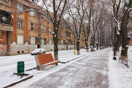 Uzhgorod, Ukraine - JAN 05, 2016: linden alley in winter. old czechlova architecture on the nezalezhnosti embankment