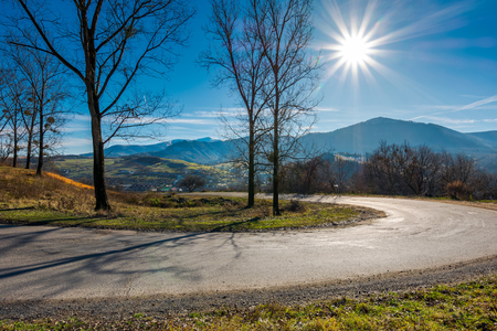 serpentine in beautiful mountainous countryside. sunny november day. tall leafless trees along the road. village down in the valley Stock Photo
