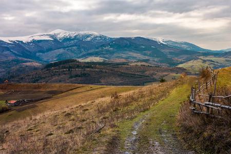 Área rural en noviembre. valla de madera por el camino rural. poderosa cresta con picos nevados en la distancia. sombrío clima otoñal