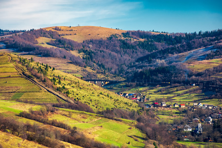 village in a valley. november weather. grassy rural fields on hills above settlement. lovely sunny day. Stock Photo
