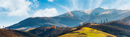 panorama of mountain ridge with snowy peak above the hill with grassy rural fields. wonderful weather condition of november Stock Photo