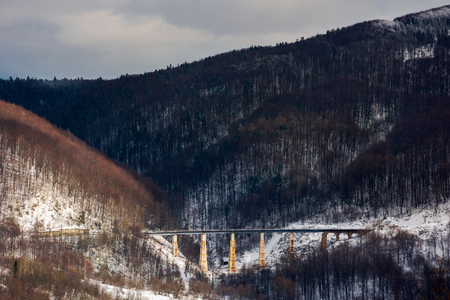 winter rail road transportation in mountains. old viaduct between the hills Stock Photo