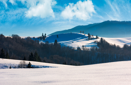 mountainous landscape on a bright winter day. wonderful cloudscape above the snow covered hills rolling hills