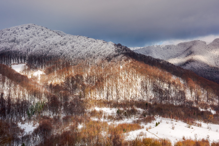 lovely winter landscape in mountains with snowy tops in dappled light and cloudy sky above the ridge. view from above