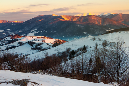winter countryside of Carpathian mountains. beautiful landscape at sunrise. rural fields on a hill covered in snow. snowy peak of distant ridge shine on the sun light. valley in blue shade Stock Photo