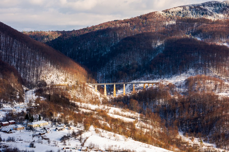 winter rail road transportation in mountains. station and village on hill and viaduct in the distance. beautiful scenery in dappled light Stock Photo