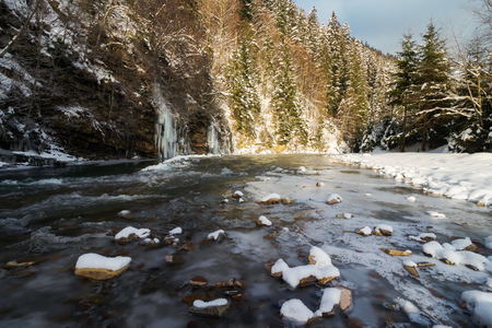 lovely winter scenery by the river. snow covered banks and trees. frozen waterfall in the distance. beautiful sunny day