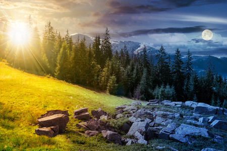 alpine summer landscape day and night time change composite. rock formation near the spruce forest on a grassy hill.  mountain with snowy top in the distance. springtime meets summer concept Stock Photo - 111916104