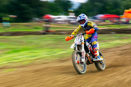 Uzhgorod, Ukraine - JUN 26, 2018: TransCarpathian Open Regional Motocross Championship. extreme sport competition. young participant accelerating. panning with slow shutter speed, motion blur effect. 版權商用圖片 - 113415496