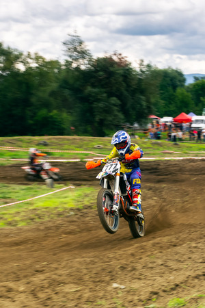 Uzhgorod, Ukraine - JUN 26, 2018: TransCarpathian Open Regional Motocross Championship. extreme sport competition. young participant accelerating after taking the turn.