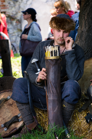 Chynadiyovo, Ukraine - May 27, 2017: medieval culture festival Silver Tatosh. Location St. Miklos Castle. Archer sitting under the tree Editorial