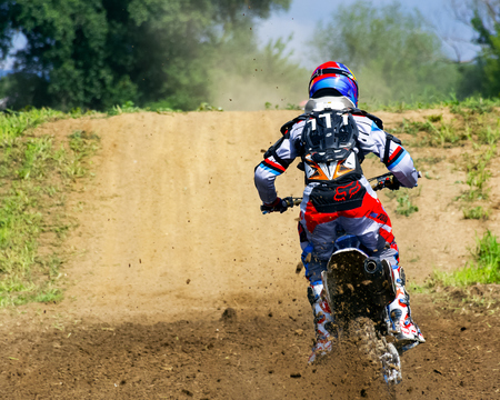 Uzhgorod, Ukraine - JUN 26, 2018: TransCarpathian Open Regional Motocross Championship. extreme sport competition. participant accelerating in the dust before the jump over the hump. view from behind