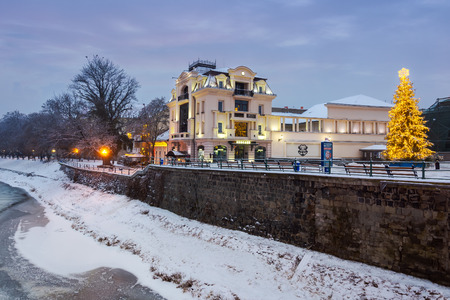Uzhgorod, Ukraine - DEC 26, 2016: christmas tree in old town at dawn. beautiful architecture on the embankment between the linden alley and theatrical square. river in ice and snow Publikacyjne