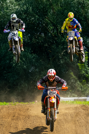 Uzhgorod, Ukraine - JUN 26, 2018: TransCarpathian Open Regional Motocross Championship. extreme sport competition. leader leave the Pursuit in the dust jumping over the hump