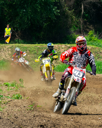 Uzhgorod, Ukraine - JUN 26, 2018: TransCarpathian Open Regional Motocross Championship. extreme sport competition. leader taking the turn leave the Pursuit in the dust
