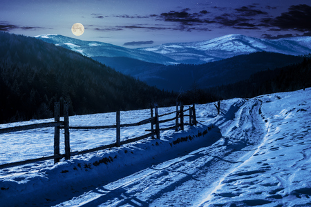 country road in to the winter mountains at night in full moon light. wooden fence along the road. composite image Stock Photo