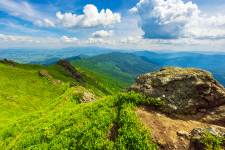 boulders on top of the ridge with grassy humps and hills. spectacular view of wide landscape spread in to the distance. good summer weather with fluffy clouds on a bright blue sky Stock Photo