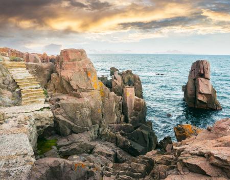gradini di pietra su scogliere rocciose a picco sul mare. splendido paesaggio di nuvole nella luce della sera Archivio Fotografico