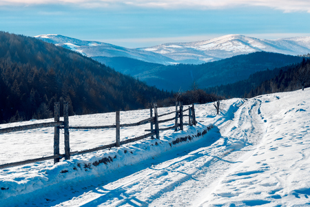 country road in to the winter mountains. wooden fence along the road. composite image Stock Photo