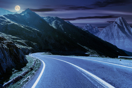 road in mountains with rocky ridge in the distance at night in full moon light. composite image. travel by car concept 스톡 콘텐츠
