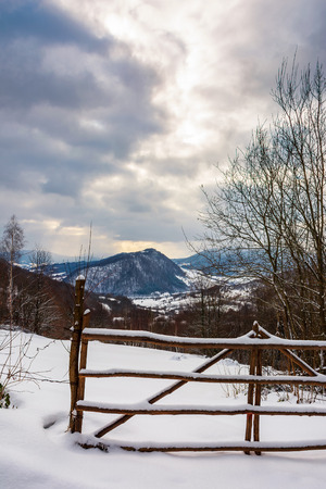 wooden fence on a snowy hill in mountains. gloomy winter weather