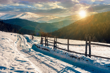 country road in to the winter mountains at sunset. wooden fence along the road. composite image Stock Photo